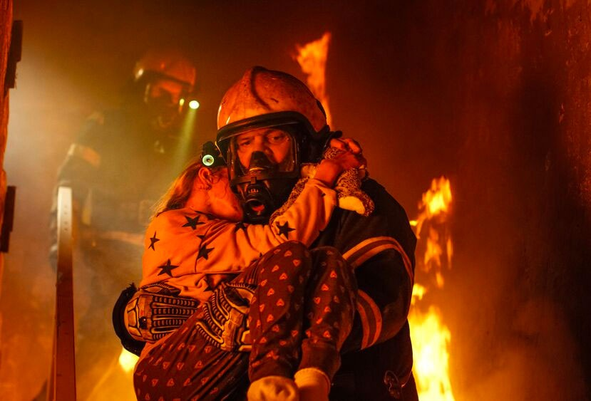 Firefighter carrying out a young girl from a burning building