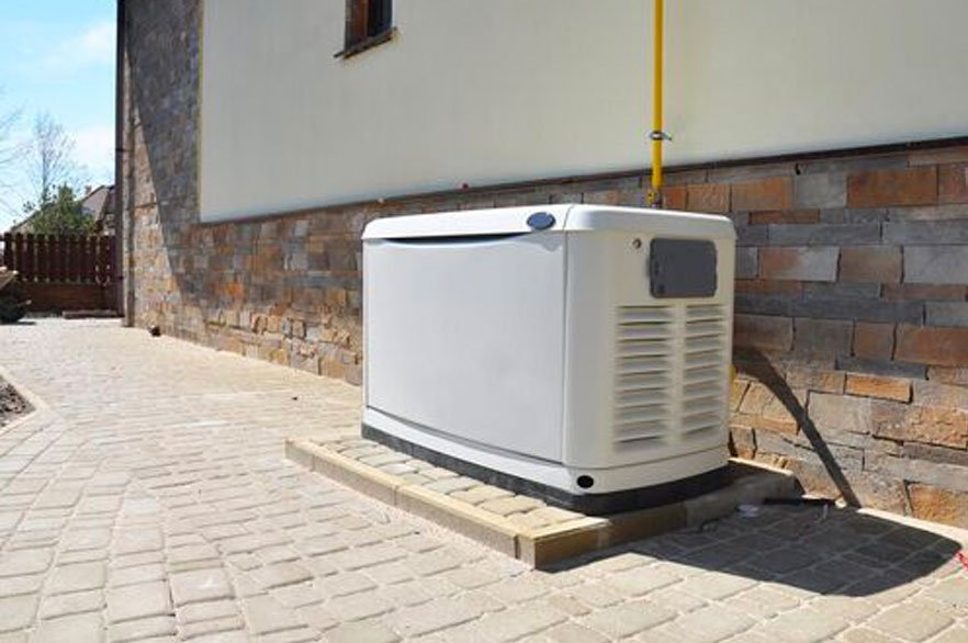 White generator on a patio outside of a house