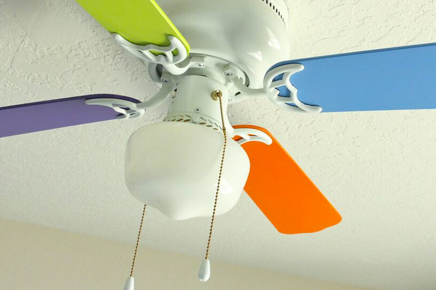 Ceiling fan in a nursery with four different colored fan blades