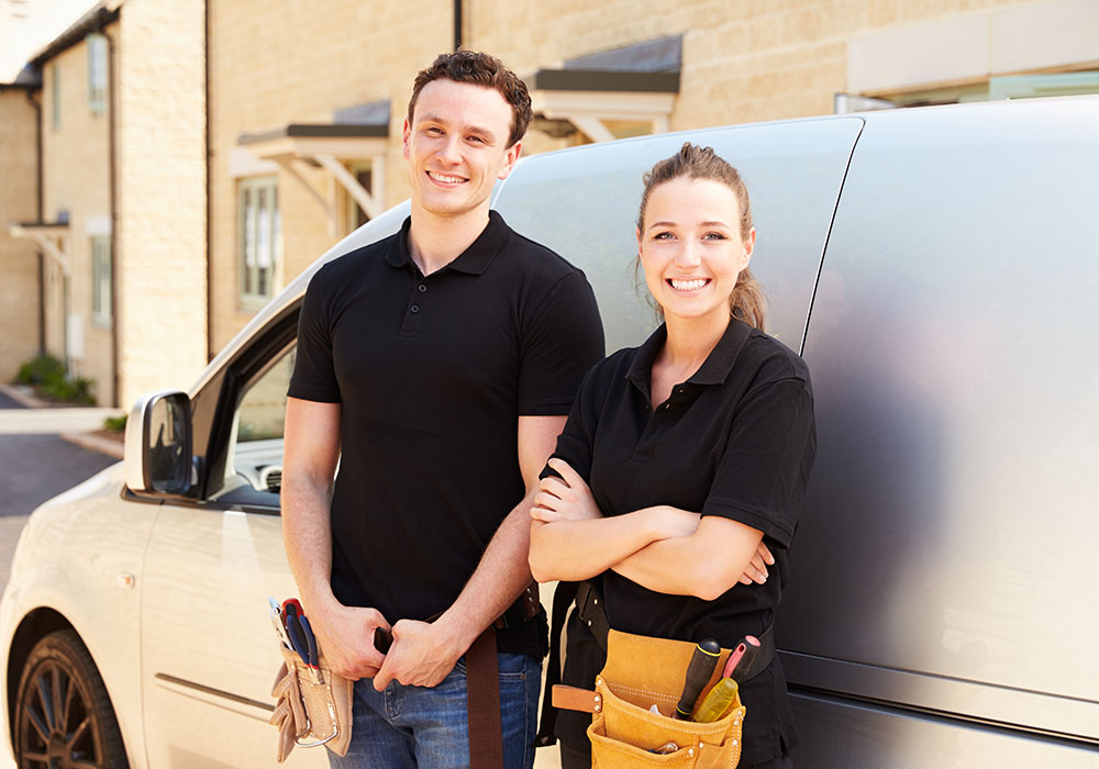 A male and female service tech wearing utility belts leaning against a service van