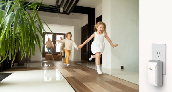Excited children running down a hallway of a new house as their parents bring in cardboard boxes in the background