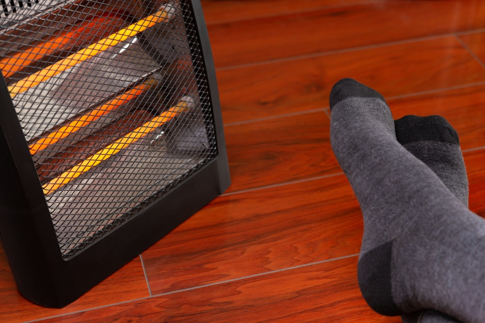 Stocking feet next to an electric space heater.