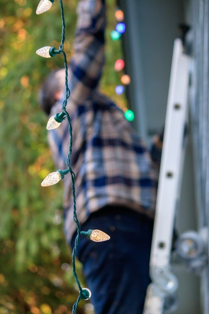 hanging decorative lights, man in background on ladder