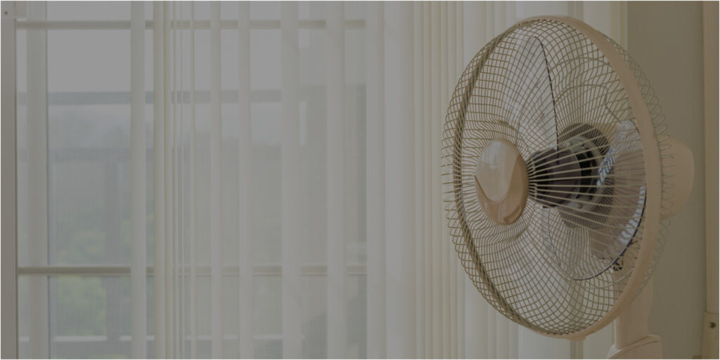 circulating stand fan next to sheer curtains
