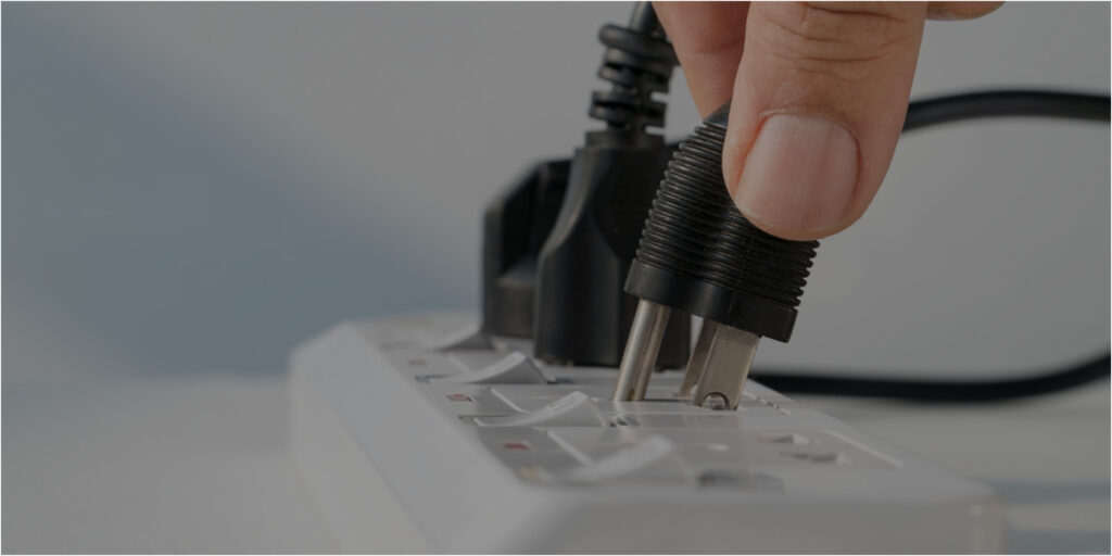 Hand placing plug in a power strip